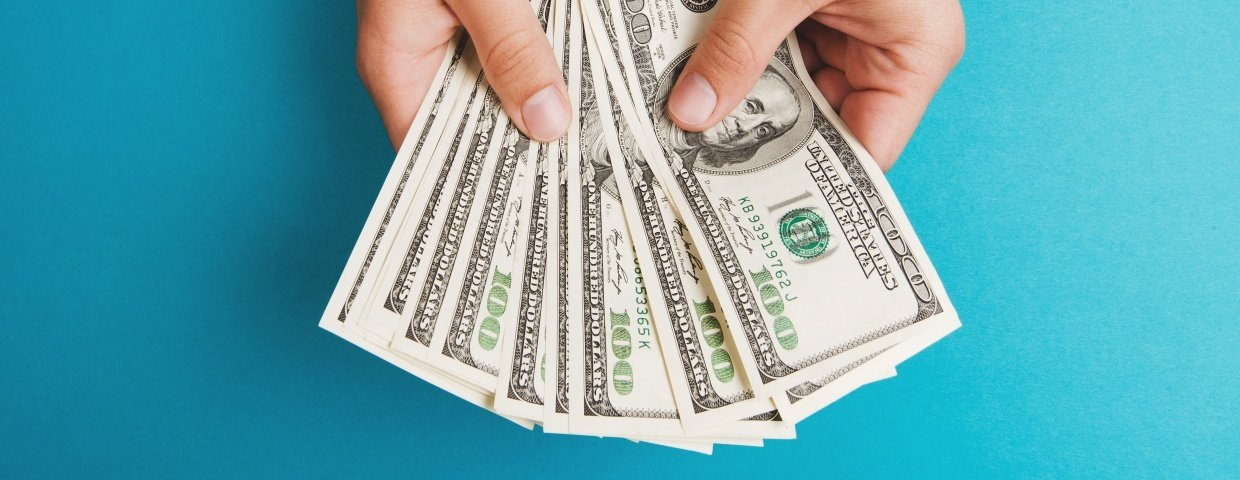 Businesses That are a Good Fit for Managed IT Services This Shows a Hand Holding Hundred Dollar Bills