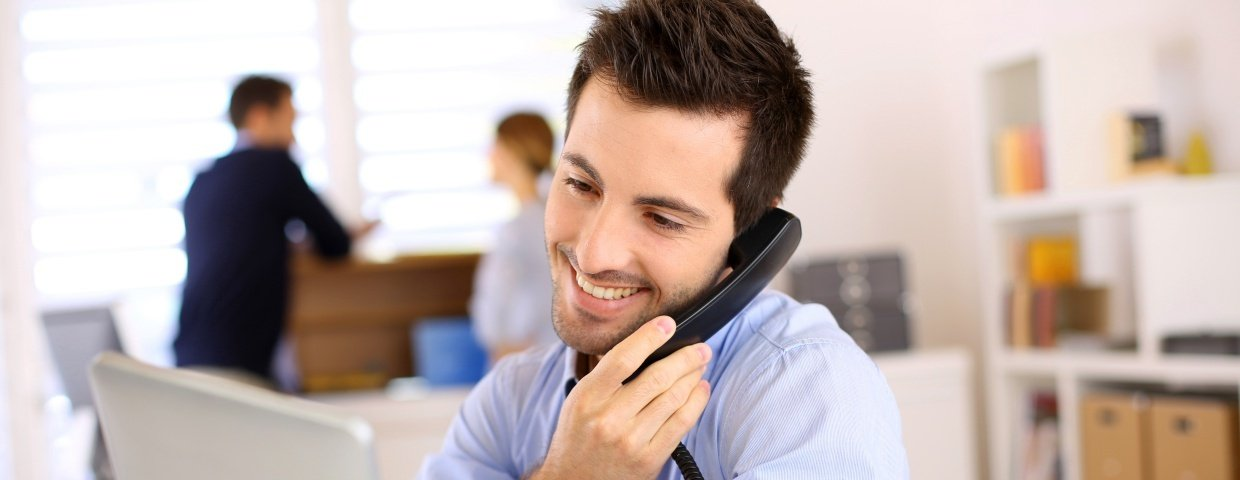 What is the Best Business Phone System- An Employee Talking on a Business Phone While Smiling
