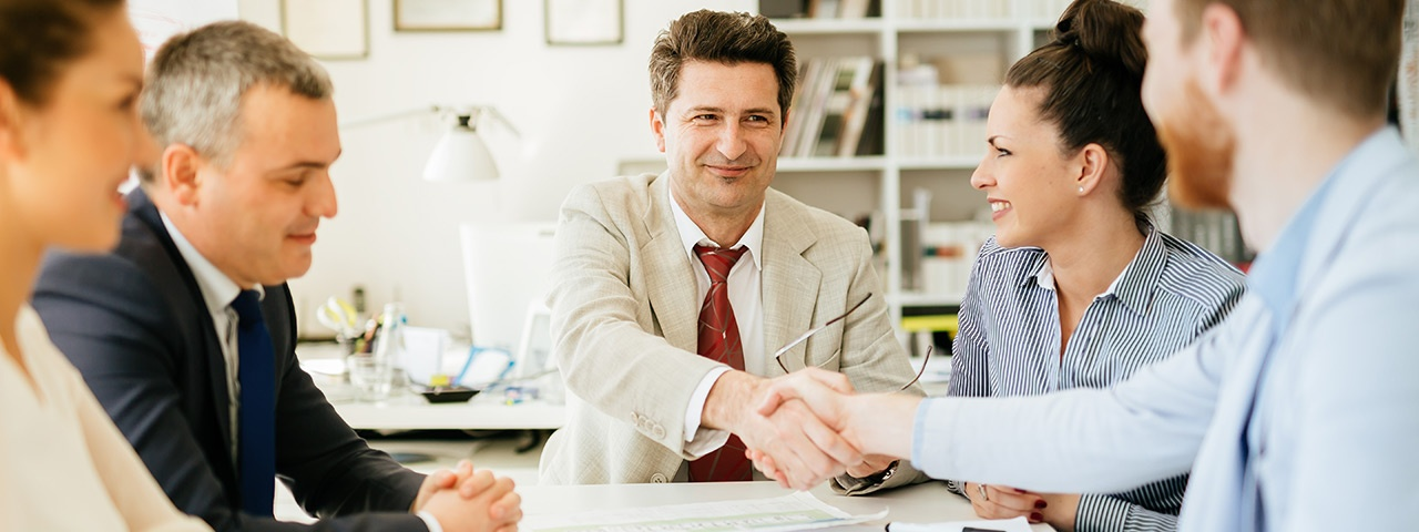 Professionals in a meeting shaking hands in agreement.